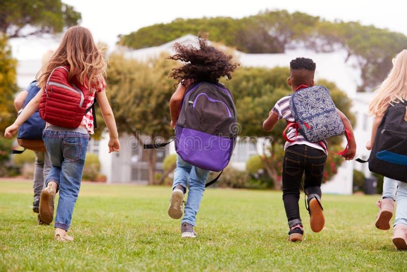 Retrovisione degli allievi della scuola elementare che si dirigono attraverso il campo al tempo della rottura immagine stock
