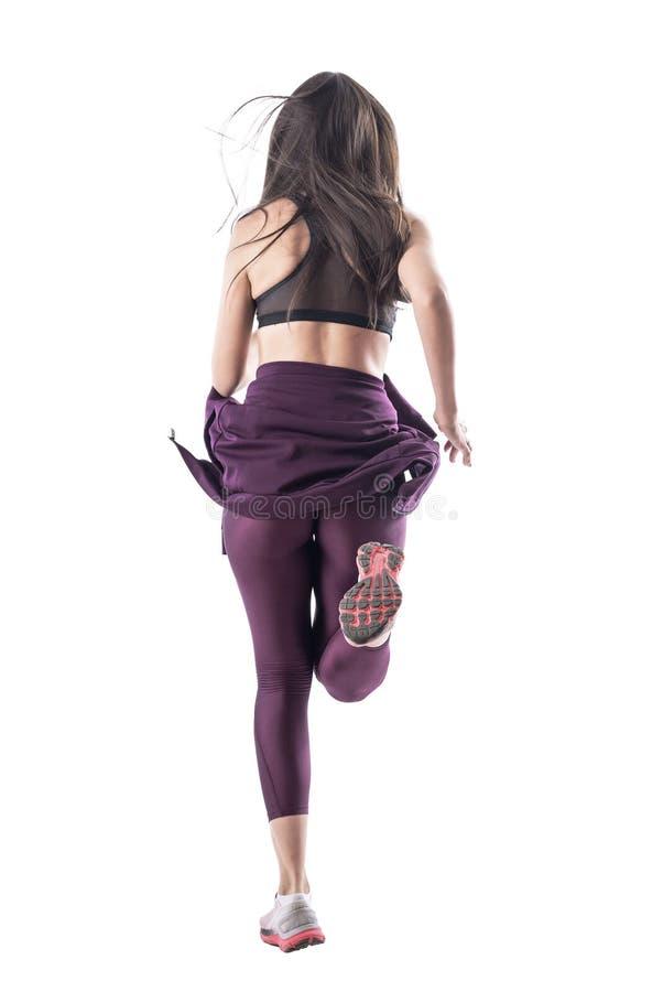 Retrovisione del corridore femminile dinamico che sprinta con i capelli ed i vestiti scorrenti immagine stock
