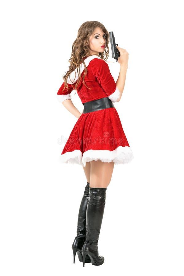 Retrovisione del fatale pericoloso del femme in testa di tornitura della pistola della tenuta del costume di Natale alla macchina fotografia stock libera da diritti
