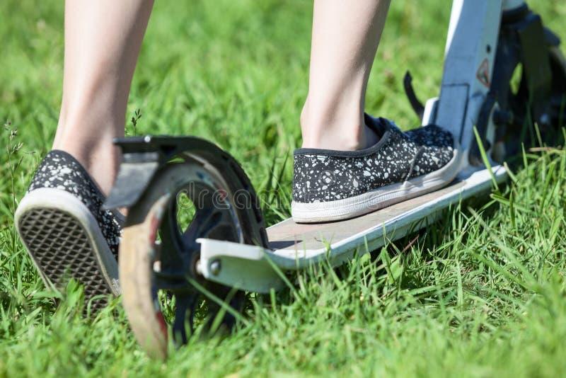 Retrovisione del primo piano del motorino di scossa di guida del bambino, erba verde sul prato di estate fotografia stock