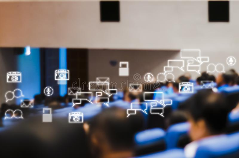 Retrovisione del pubblico che presente che incontra seminario di affari nell'auditorium con le icone sociali immagini stock