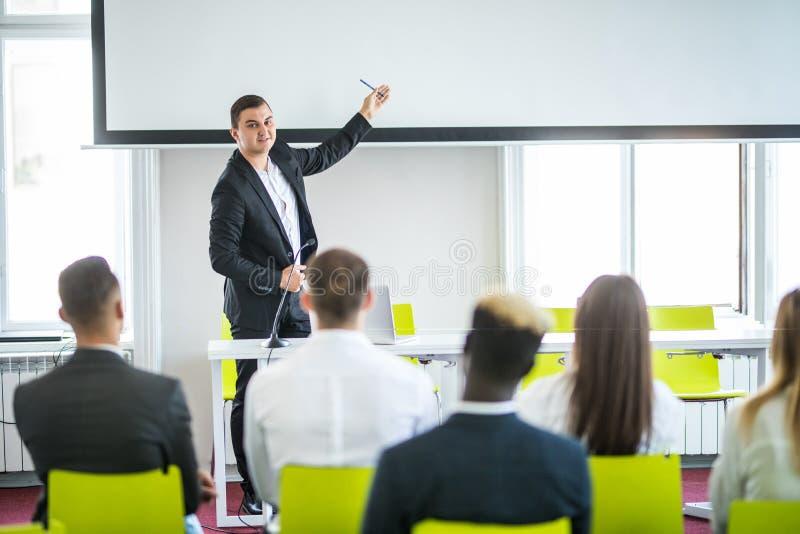 Retrovisione del pubblico nella riunione della sala per conferenze o di seminario che hanno altoparlanti sulla fase, sull'affare  fotografia stock libera da diritti