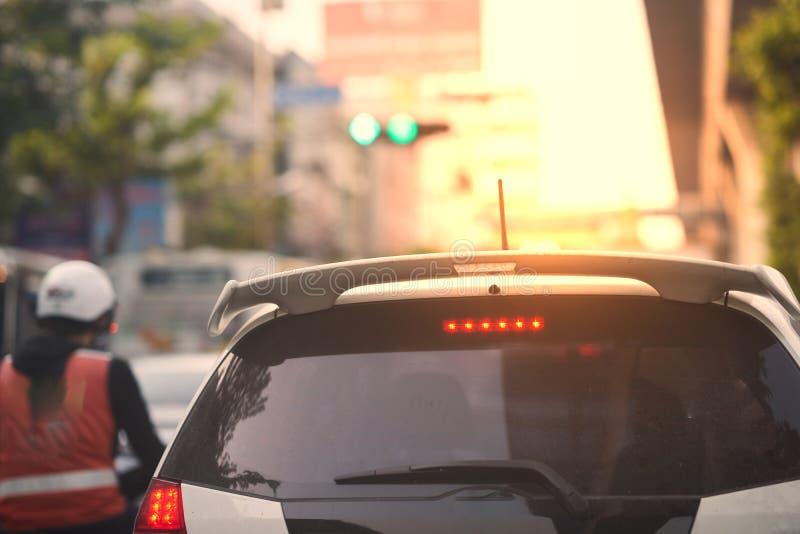 Retrovisione dell'automobile sulla via e sul semaforo con il motociclo assunto immagini stock