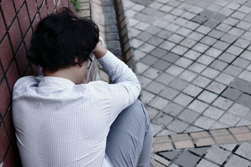 Retrovisione dell'uomo asiatico esaurito frustrato di affari nella depressione con le mani sulla fronte fotografia stock libera da diritti