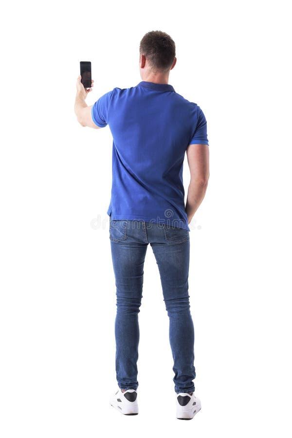 Retrovisione dell'uomo casuale adulto moderno che prende foto con lo Smart Phone fotografia stock libera da diritti
