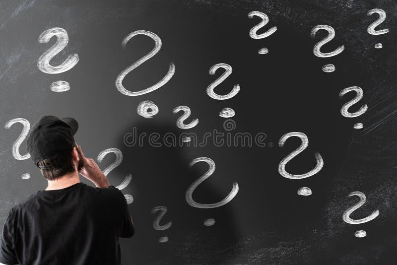 Retrovisione dell'uomo che esamina lavagna riempita di punti interrogativi fotografia stock libera da diritti