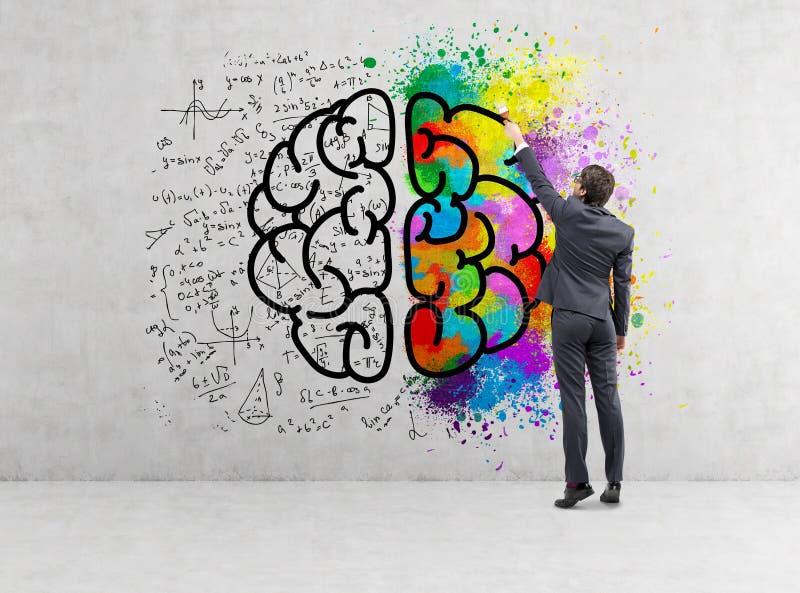 Retrovisione dell'uomo d'affari che disegna l'icona variopinta del cervello su calcestruzzo fotografia stock