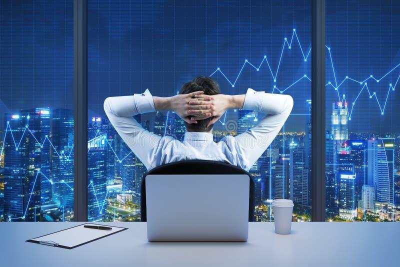 Retrovisione dell'uomo d'affari di seduta che sta esaminando la città dall'ufficio panoramico moderno Vista di sera di New York fotografie stock libere da diritti