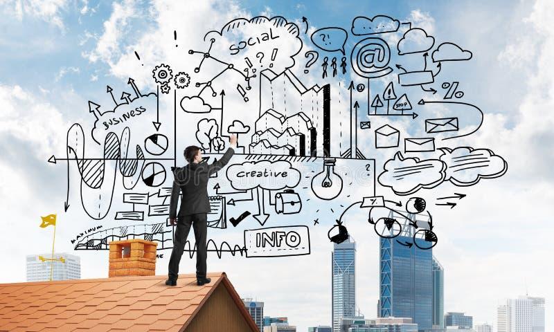 Retrovisione dell'uomo d'affari sul tetto della casa che disegna la sua nuova strategia aziendale Media misti immagine stock