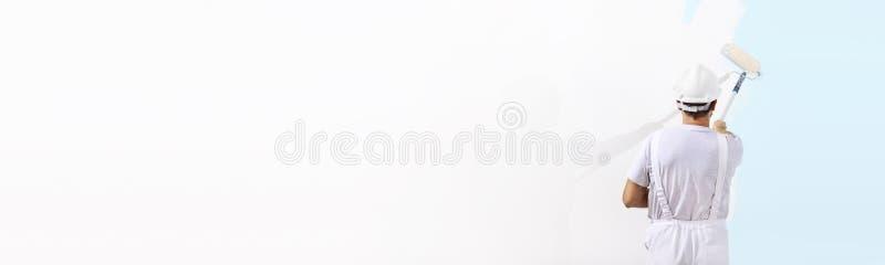 Retrovisione dell'uomo del pittore che dipinge il blu sulla parete in bianco, con la p fotografia stock