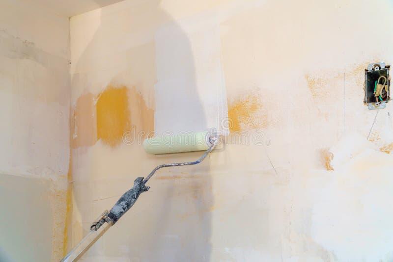 Retrovisione dell'uomo del pittore che dipinge le pareti con il rullo di pittura fotografia stock