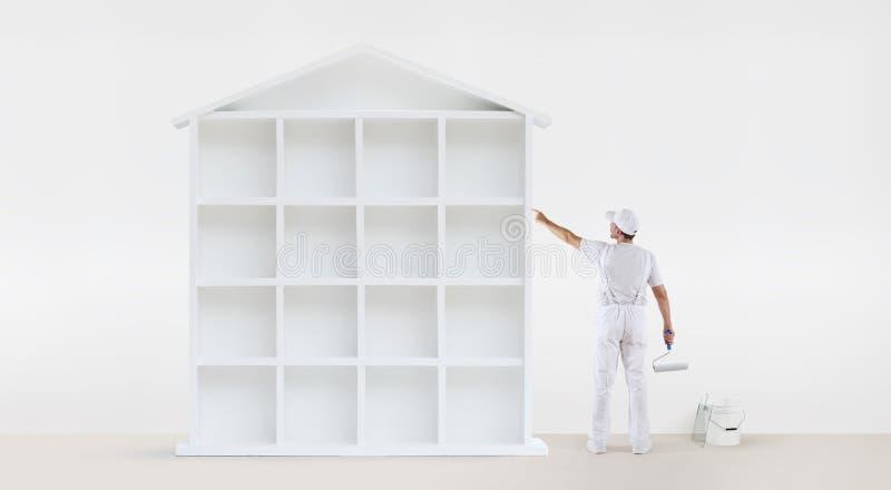 Retrovisione dell'uomo del pittore che indica con il dito la casa bianca Mo immagini stock libere da diritti