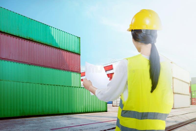 Retrovisione della donna asiatica del lavoratore con il casco giallo che controlla il programma di spedizione sul porto industria immagini stock libere da diritti