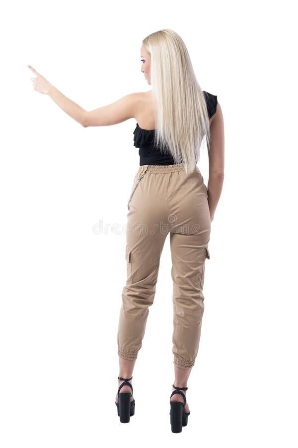 Retrovisione della donna bionda alla moda dei capelli diritti che sceglie o che seleziona con il gesto del dito immagine stock libera da diritti