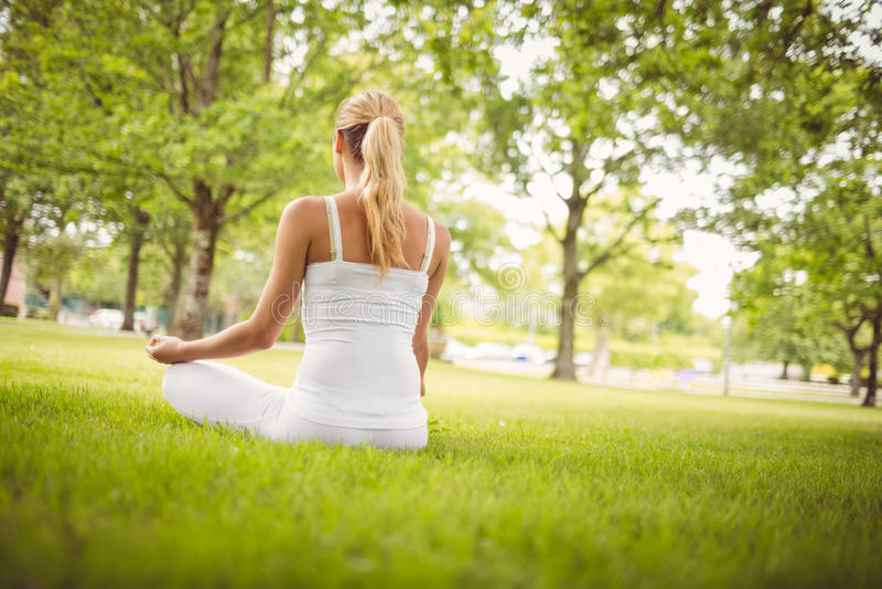 Retrovisione della donna che medita mentre sedendosi nella posa del loto fotografia stock