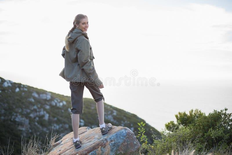 Retrovisione della donna che sta sulla pietra che guarda indietro fotografia stock