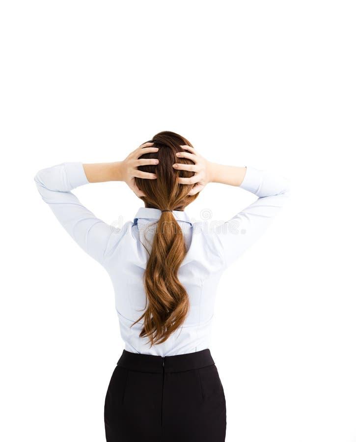 Retrovisione della donna di affari preoccupata che tiene la sua testa fotografia stock