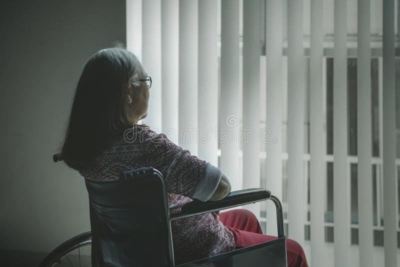 Retrovisione della donna invecchiata che guarda fuori la finestra immagini stock