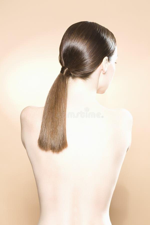 Retrovisione della donna nuda con i capelli di Brown immagini stock