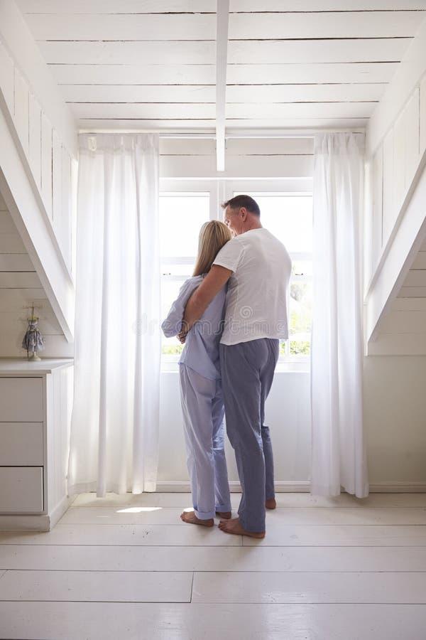 Retrovisione della finestra facente una pausa della camera da letto delle coppie affettuose fotografia stock