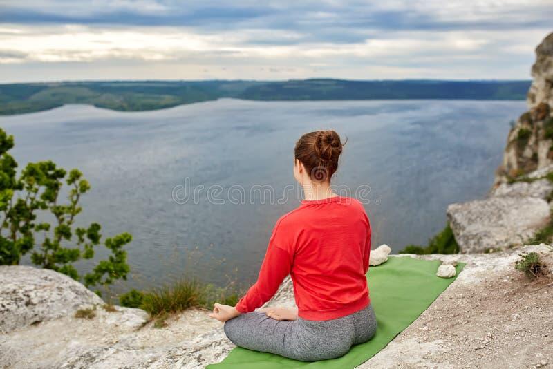 Retrovisione della giovane donna che si siede nella posizione di loto sulla roccia sopra il fiume fotografia stock