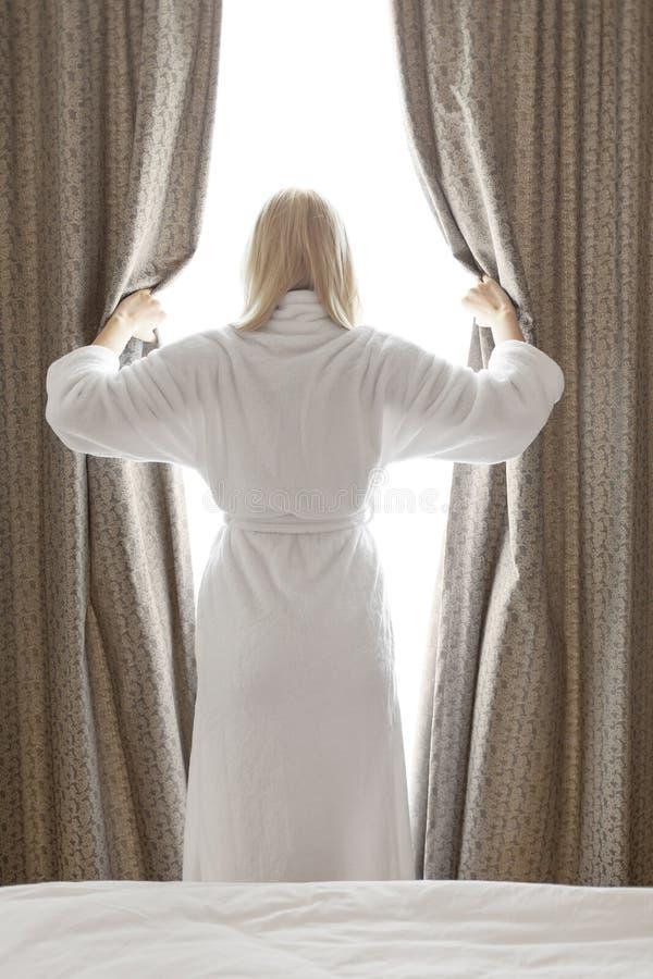Retrovisione della giovane donna in tende della camera da letto di apertura dell'accappatoio a camera di albergo immagini stock libere da diritti