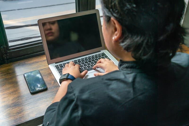 Retrovisione della lesbica asiatica che per mezzo del computer portatile accanto al cellulare fotografia stock libera da diritti