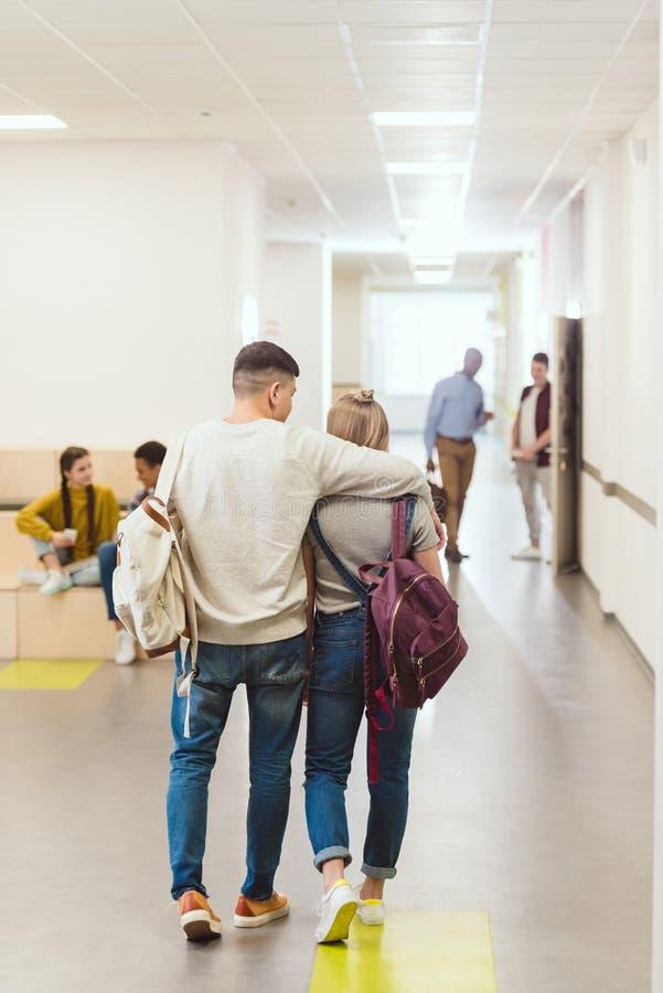 retrovisione delle coppie adolescenti degli studenti che camminano dal corridoio della scuola immagini stock