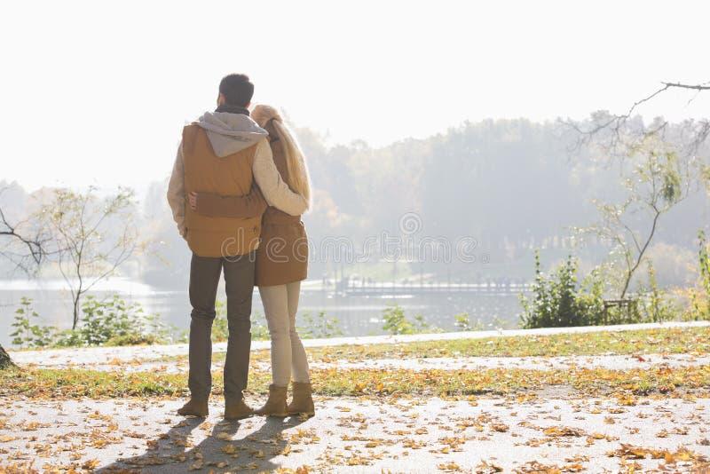 Retrovisione delle coppie che esaminano lago in parco durante l'autunno fotografia stock libera da diritti