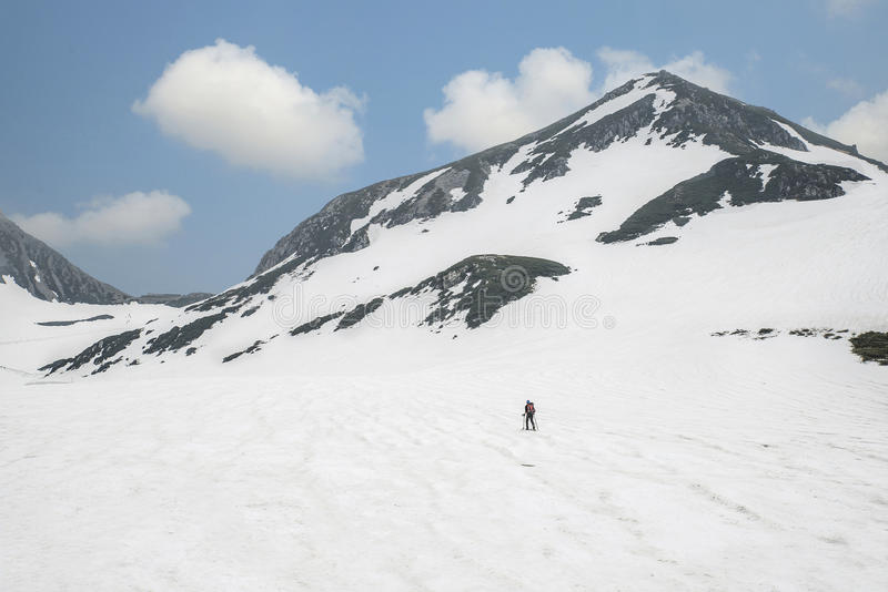 Retrovisione dello sciatore che cammina attraverso le montagne della neve, Giappone fotografie stock libere da diritti