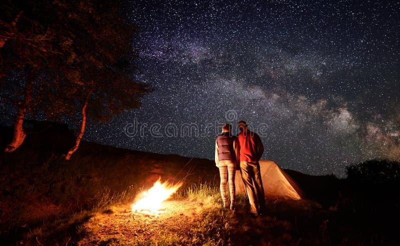 Retrovisione di aderenza per due persone l'un l'altro sguardo al cielo stellato con la Via Lattea fotografie stock
