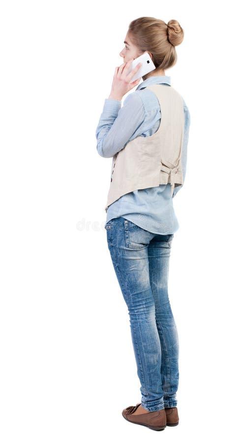 Retrovisione di bella giovane donna con un telefono cellulare immagine stock libera da diritti