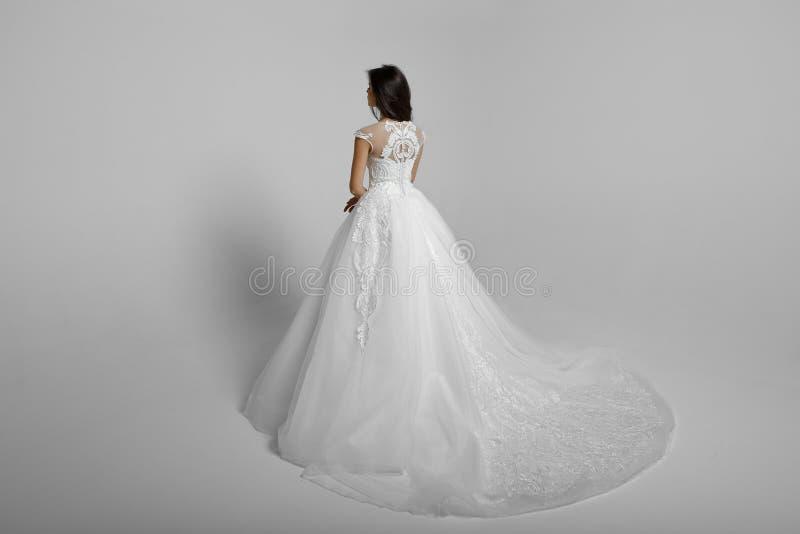 Retrovisione di bella giovane donna in vestito bianco da principessa di nozze, su un fondo bianco Vista orizzontale fotografia stock libera da diritti