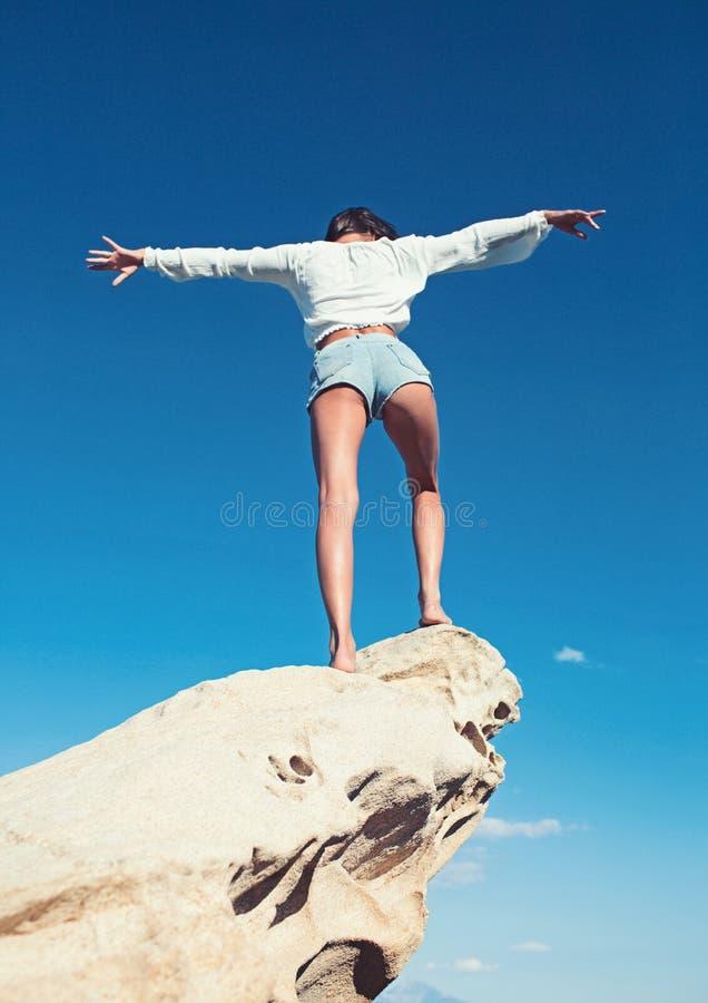 Retrovisione di bella, ragazza castana con le mani sollevate, esaminanti oceano Concetto di libertà, festa sulla spiaggia immagine stock libera da diritti