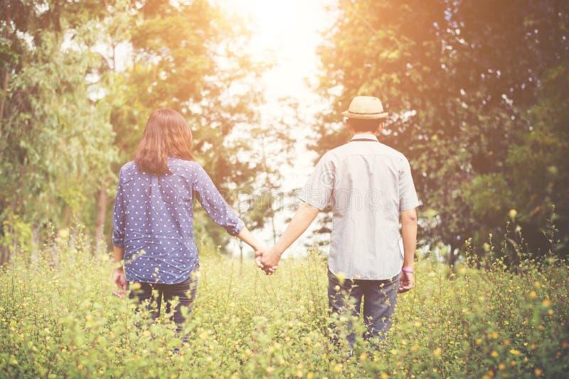 Retrovisione di giovane donna dei pantaloni a vita bassa che cammina con il suo ragazzo sul g immagini stock libere da diritti