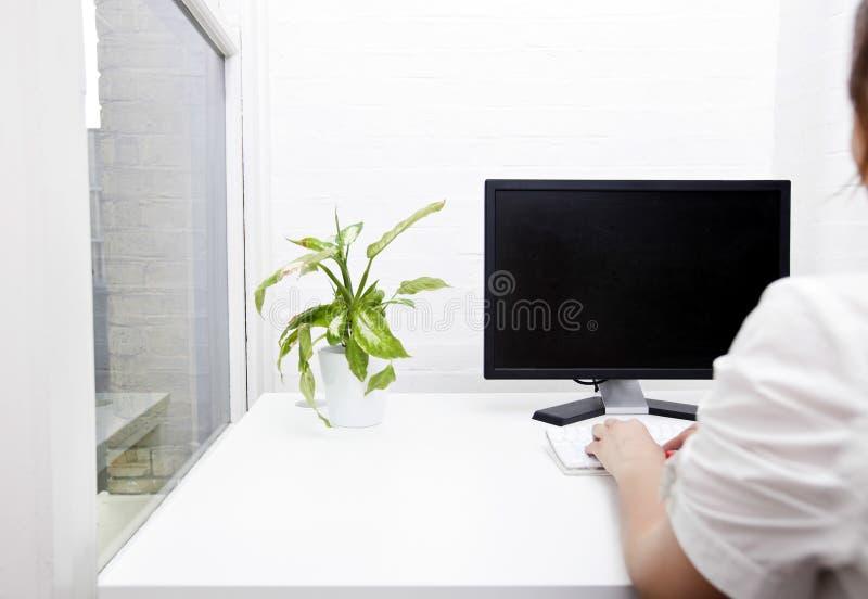 Retrovisione di giovane donna di affari che per mezzo del computer allo scrittorio immagine stock libera da diritti