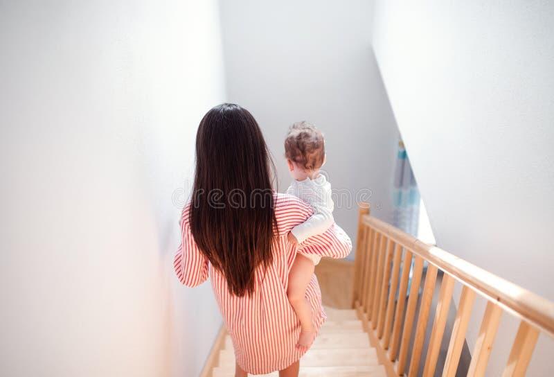 Retrovisione di giovane madre che porta il piccolo figlio del bambino giù le scale all'interno a casa fotografia stock libera da diritti