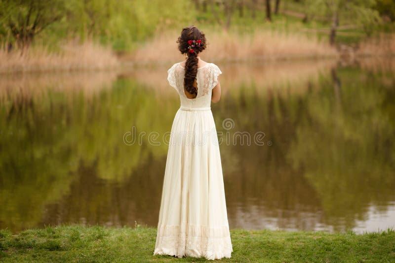 Retrovisione di giovane sposa anonima in un bello vestito da sposa pieno, con l'acconciatura, guardante giù, fondo della natura immagini stock