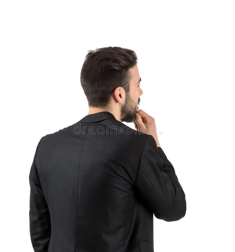 Retrovisione di giovane tipo barbuto che esamina parete bianca fotografia stock