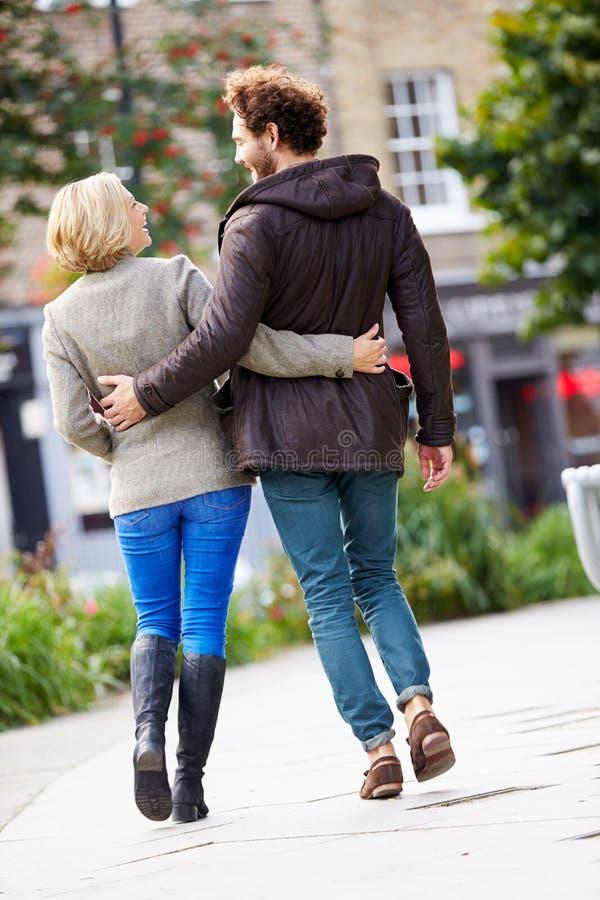 Retrovisione di giovani coppie che camminano insieme attraverso il parco della città immagine stock