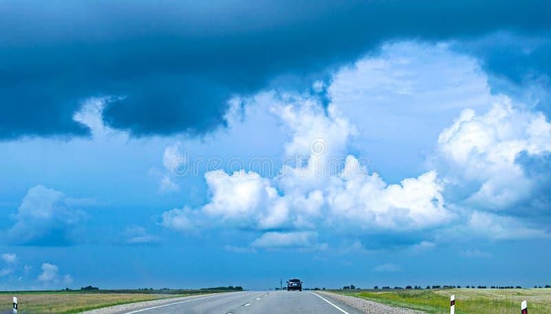Retrovisione di un'automobile che accelera sulla strada asfaltata in campagna fotografie stock libere da diritti
