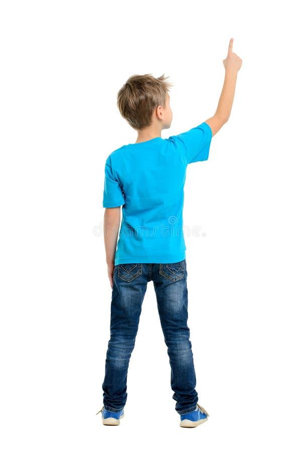 Retrovisione di un ragazzo di scuola sopra fondo bianco che indica verso l'alto fotografie stock
