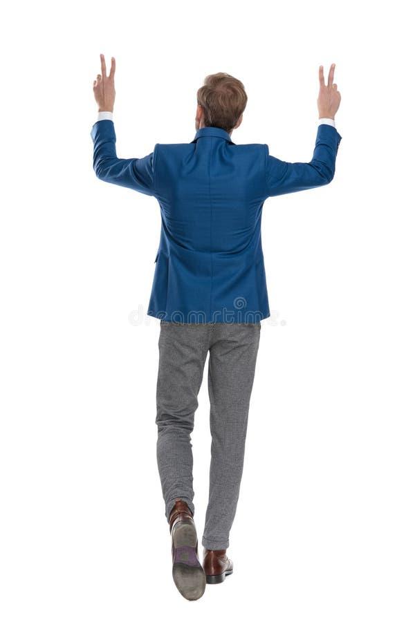 Retrovisione di un uomo casuale che cammina e che gesturing pace fotografia stock libera da diritti