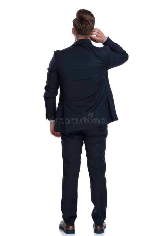 Retrovisione di un uomo d'affari domandantesi che graffia il suo collo immagine stock