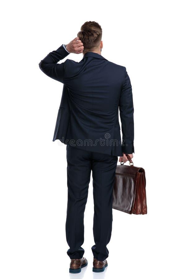 Retrovisione di un uomo d'affari incerto che tiene la sua valigia fotografia stock libera da diritti