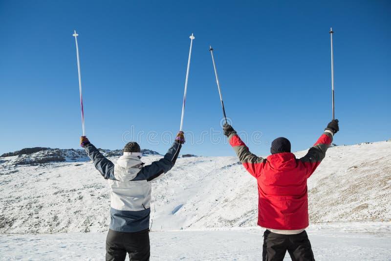 Retrovisione di una coppia che alza i pali di sci su neve immagini stock libere da diritti
