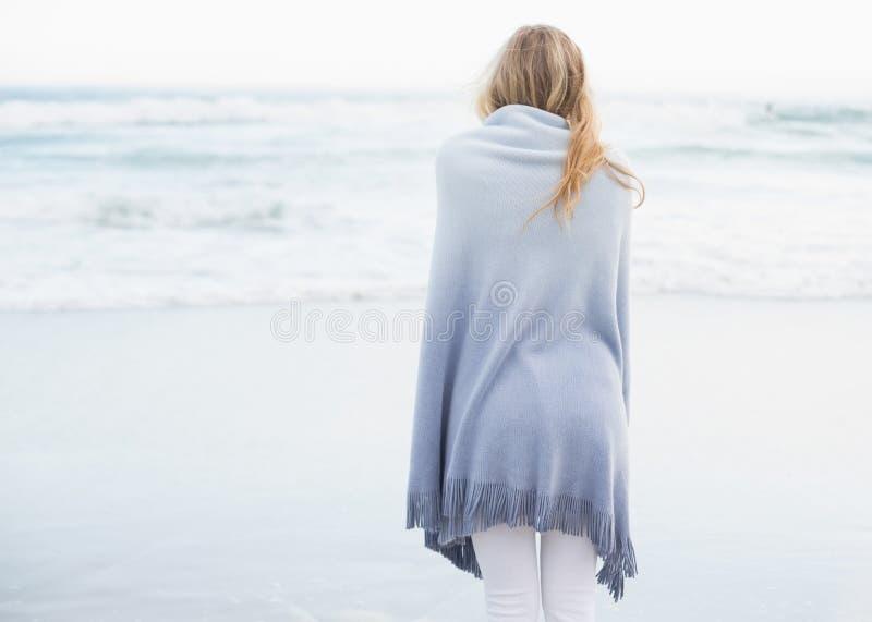 Retrovisione di una donna bionda che si scalda in una coperta immagini stock libere da diritti
