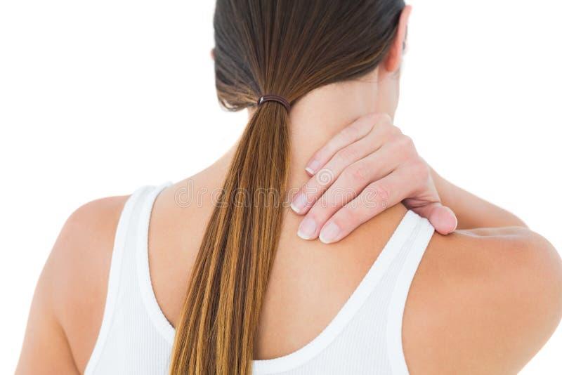 Retrovisione di una donna casuale che soffre dal dolore del collo immagini stock libere da diritti