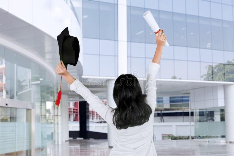 Retrovisione di una donna che celebra la sua graduazione fotografia stock