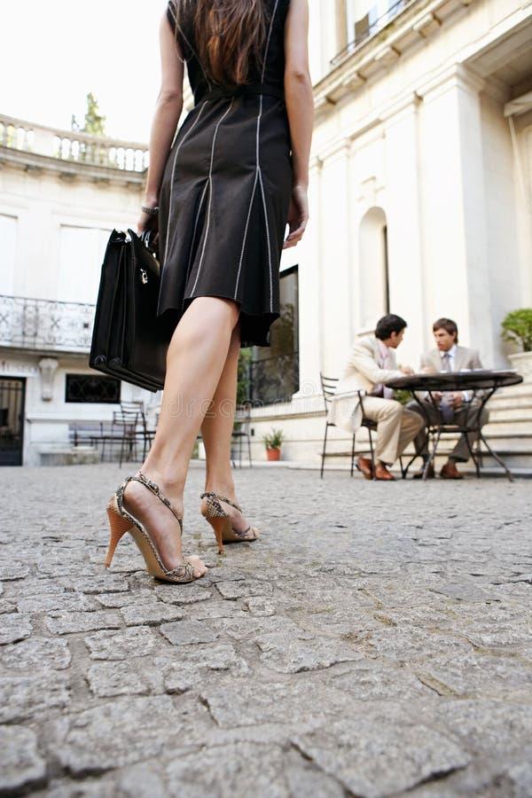 Gambe della donna di affari che camminano alla riunione. immagine stock